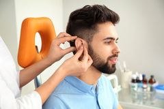 Otolaryngologist putting hearing aid in patient`s ear. At clinic stock images