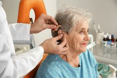 Otolaryngologist putting hearing aid in senior patient`s ear. At clinic stock photo
