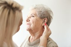 Otolaryngologist putting hearing aid in senior woman's ear on light background royalty free stock photography