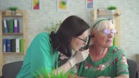 Otolaryngologisten undersöker örat av en gammal kvinna med hjälpen av en otoscope arkivfilmer