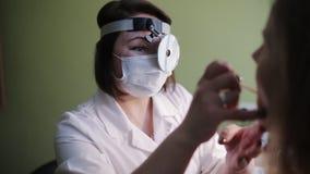 Otolaryngologisten undersöker struphuvudet av patienten i kontoret lager videofilmer