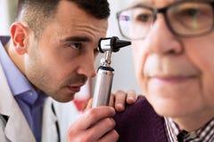 Otologist che esamina orecchio paziente fotografia stock
