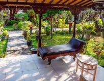 Otomana na werandzie Indonezyjski bungalow w bujny zieleni ogródzie fotografia stock