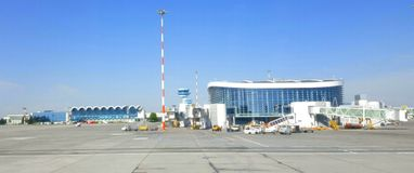 Otopeni Airport, Bucharest, Romania. Tarmac, terminal and gates of Otopeni Airport, Bucharest, Romania on sunny day against blue skies Royalty Free Stock Images
