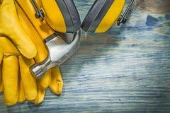 Otoprotettori del martello da carpentiere dei guanti di sicurezza sul constru del bordo di legno Fotografia Stock Libera da Diritti