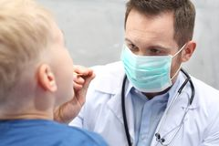 Otorinolaringoiatra, un bambino con un medico fotografie stock libere da diritti
