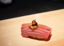 Otoro (buk för bluefintonfisk) sushi som överträffas med havsgatubarnet (uni), kaviaren och den guld- flingan Arkivfoton