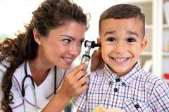 Otoskopu uszaty egzamin wykonujący młodą lekarką fotografia stock