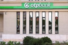 OTP Bank in Hungary. KESZTHELY, HUNGARY - AUGUST 11: People reflect in OTP Bank branch on August 11, 2012 in Keszthely, Hungary. OTP is the biggest commercial Stock Image