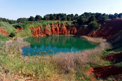 Otranto Bauxite Mine. A natural amazing green lake created in an adondoned bauxite mine with intense red rock walls Royalty Free Stock Images