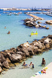 Otranto, Italy. Ionian sea with rocks, harbor, boats and people on vacation. Royalty Free Stock Image