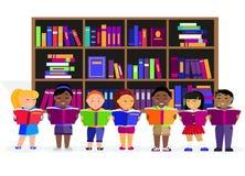 Otros niños leyeron los libros en biblioteca Foto de archivo