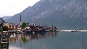 Otta sjösikt med kyrkor av Hallstatt i Österrike fjällängar med traditionella byggnader, berg och fartyg på arkivfilmer
