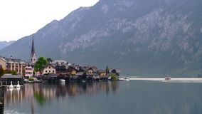 Otta sjösikt med kyrkor av Hallstatt i Österrike fjällängar med traditionella byggnader, berg och fartyg på lager videofilmer