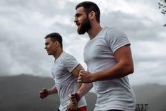 Ottagenomkörare, sportive män som kör i berg som bor sund livsstil arkivfoto