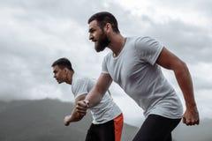 Ottagenomkörare, sportive män som kör i berg som bor sund livsstil fotografering för bildbyråer