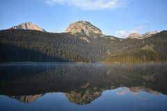 Ottapanoraman av det Durmitor berget och reflexionen i den svarta sjön Royaltyfria Foton