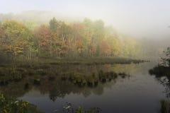 Ottasoluppgång över en sjö Arkivbild