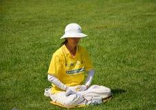 OTTAWA, CANADA - AUGUSTUS 19, 2014: Vrouw die Falun-Gong uitoefenen De Falungong of Falun Dafa zijn een Chinese geestelijke prakt stock afbeeldingen