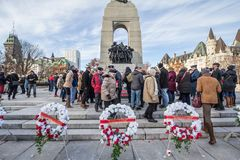 Crowd of Canadian war Veterans standing behind funeral wreath  on National War memorial, on remembrance day. OTTAWA, CANADA - NOVEMBER 11, 2018:..Picture of a stock photos