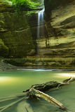 Ottawa Canyon, Starved Rock State Park, Illinois. Waterfall and cliff walls with tree trunk as the summer morning light hits the sandstone canyon.  Ottawa Stock Photo