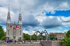 Notre Dame cathedral and Maman spider scuplture in Ottawa, Canad. OTTAWA, ONTARIO - July 08, 2017: Notre Dame cathedral and Maman spider scuplture in Ottawa Royalty Free Stock Images