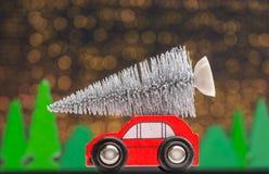 Ottenendo un albero di Natale presentato con un'automobile di legno davanti al fondo di Natale immagini stock libere da diritti