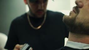 Ottenere forma perfetta Vista laterale del primo piano di giovane uomo barbuto che ottiene taglio di capelli della barba dal parr archivi video