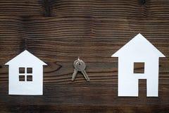Ottenga un'ipoteca Alloggi la siluetta vicino alle chiavi dell'appartamento sul copyspace di legno scuro di vista superiore del f Fotografia Stock Libera da Diritti