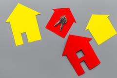 Ottenga un'ipoteca Alloggi la siluetta vicino alle chiavi dell'appartamento sul copyspace grigio di vista superiore del fondo Immagine Stock Libera da Diritti