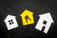 Ottenga un'ipoteca Alloggi la siluetta vicino alle chiavi dell'appartamento sulla vista superiore del fondo nero Fotografia Stock Libera da Diritti