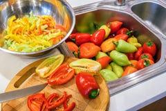 Ottenimento di autunno del raccolto dei peperoni Intero, dimezzato ed affettato in fette longitudinali pepa fotografia stock