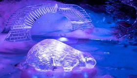 Otter and Bridge. London, United Kingdom - December 29 2018: An ice sculpture of an otter and a bridge in the Winter Wonderland Magical Ice Kingdom off Park Lane royalty free stock image