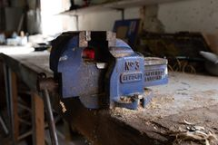 Ottery St Mary, Devon, Engalnd, March, 2, 2019: A close up of a used working blue vice on a wooden worktop in a workshop covered royalty free stock photos