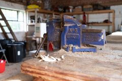 Ottery St Mary, Devon, Engalnd, March, 2, 2019: A close up of a used working blue vice on a wooden worktop in a workshop covered. Ottery St Mary, Devon, Engalnd royalty free stock photography