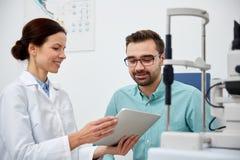 Ottico con il pc ed il paziente della compressa alla clinica di occhio Fotografia Stock Libera da Diritti