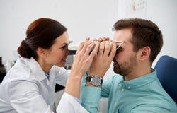 Ottico con il pupilometer e paziente alla clinica di occhio Fotografia Stock Libera da Diritti