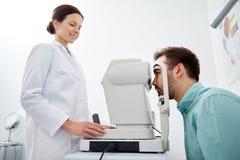 Ottico con il tonometer e paziente alla clinica di occhio Fotografie Stock Libere da Diritti