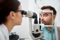 Ottico con il tonometer e paziente alla clinica di occhio Fotografie Stock
