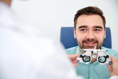 Ottico con la struttura di prova e paziente alla clinica Immagini Stock