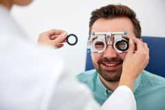 Ottico con la struttura di prova e paziente alla clinica Fotografie Stock