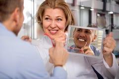 Ottico femminile che consulta cliente maschio maturo usando uno specchio immagini stock