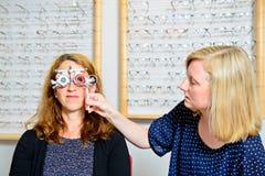 Ottico femminile che controlla gli occhi della donna per vedere se c'è nuovi vetri Fotografia Stock Libera da Diritti