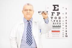Ottico maschio che tiene i vetri davanti ad un grafico di occhio Immagini Stock Libere da Diritti