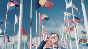 Ottimista esamini una clip concettuale futura di promessa contro lo sfondo di chiari cielo e bandiere nazionali di stock footage