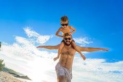Otto anni del ragazzo che si siede sul ` s del papà mette Entrambi in shorts ed occhiali da sole di nuoto, divertendosi sulla spi Immagini Stock Libere da Diritti