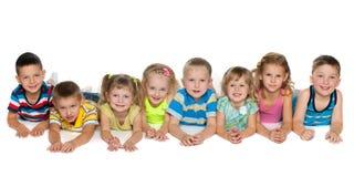 Otto bambini che si trovano sul pavimento Fotografie Stock Libere da Diritti