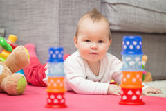 Otto mesi della neonata che mette sul pavimento Immagine Stock
