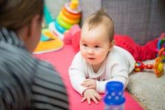 Otto mesi della neonata che mette sul pavimento Fotografia Stock Libera da Diritti