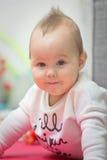Otto mesi della neonata che mette sulla sua pancia sul pavimento Fotografia Stock